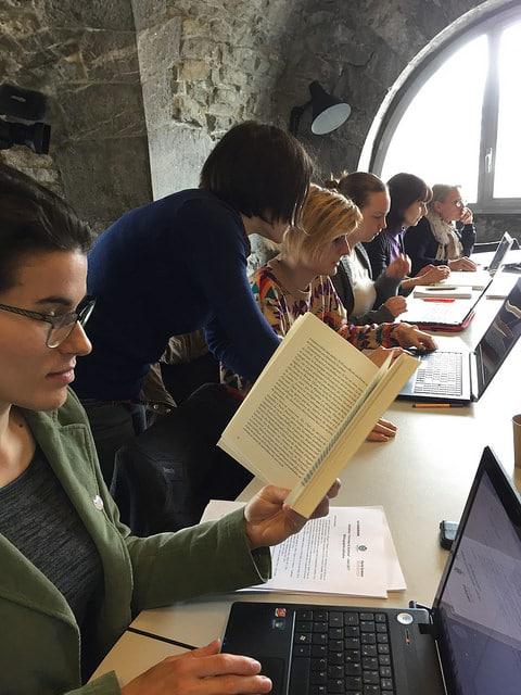 Une participante en pleine édition pendant qu'une Wikipédienne avertie discute avec une débutante